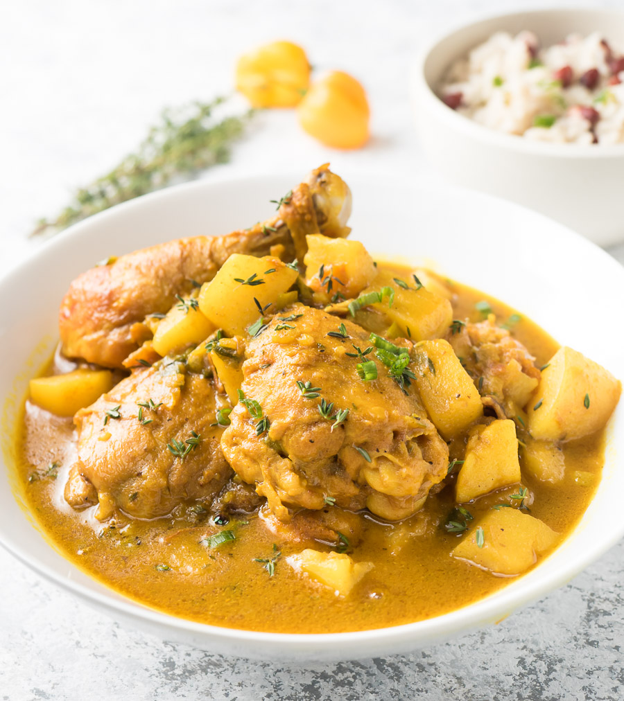Jamaican curry chicken in a white bowl from the front.