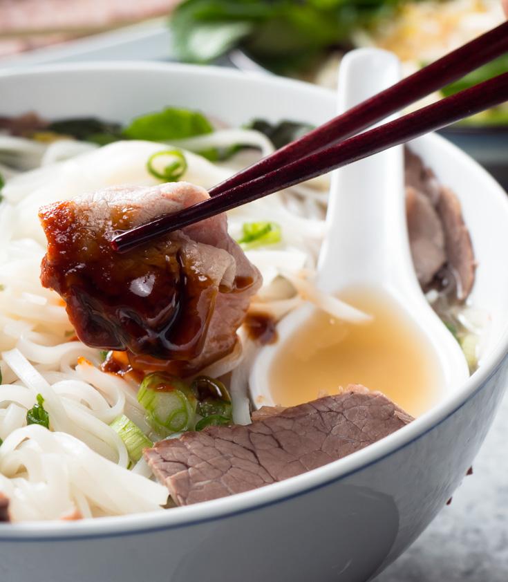Beef slice dipped in hoisin held by chopsticks.