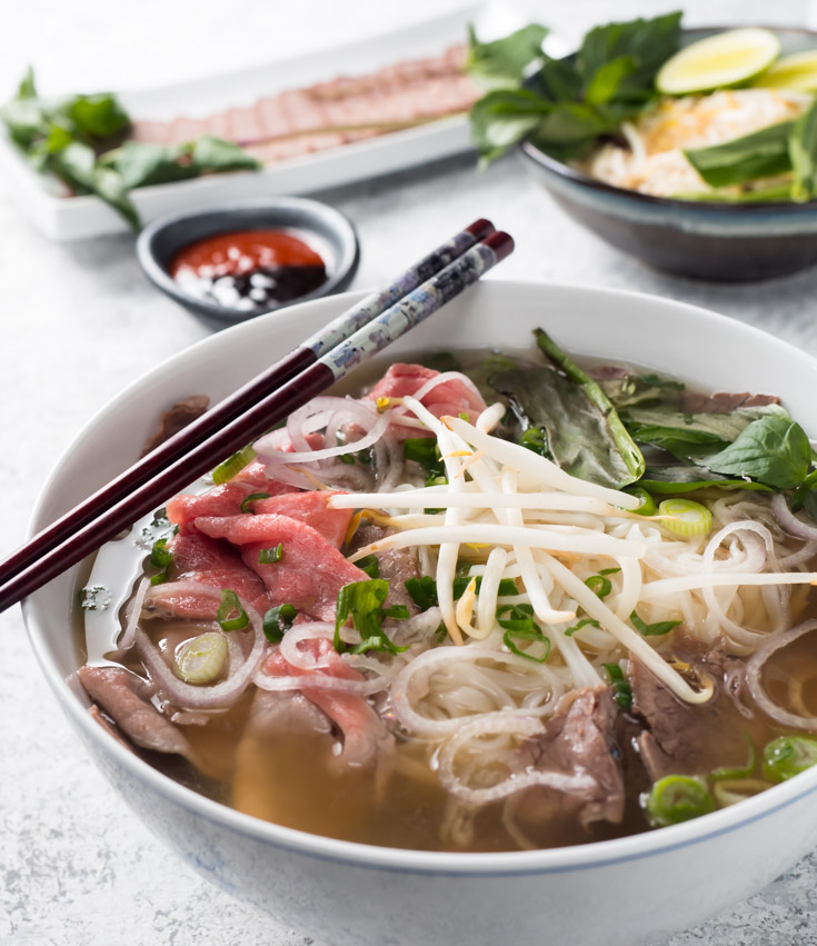 Bowl of beef pho with chopsticks from the front.