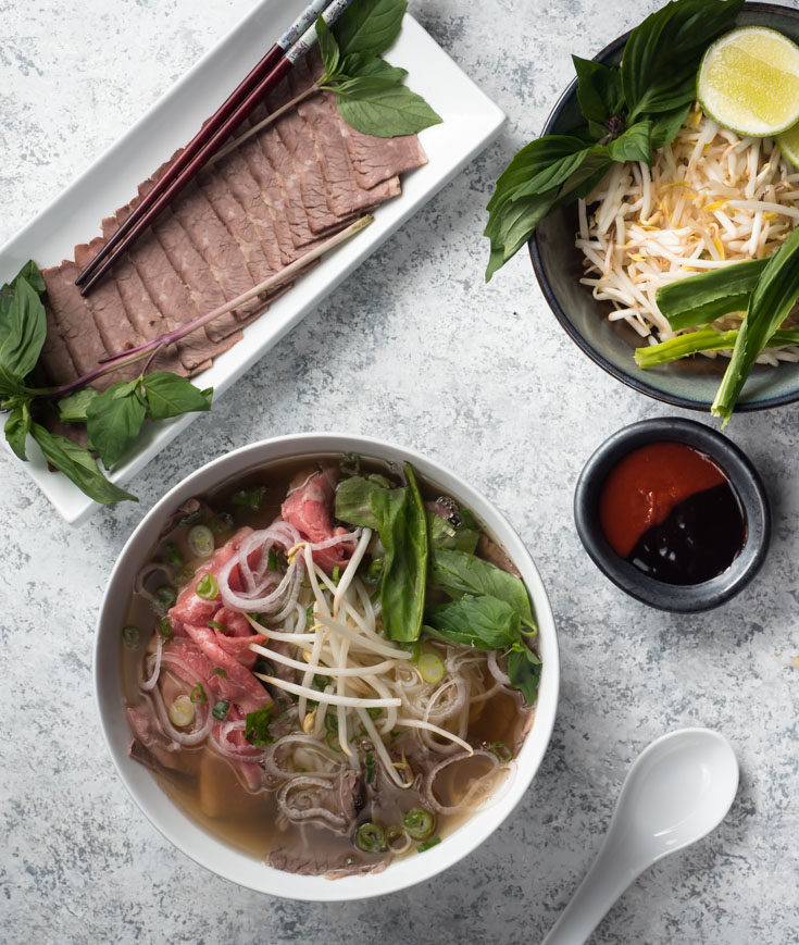 Bowl of beef pho, plate of brisket slices and garnishes from above.