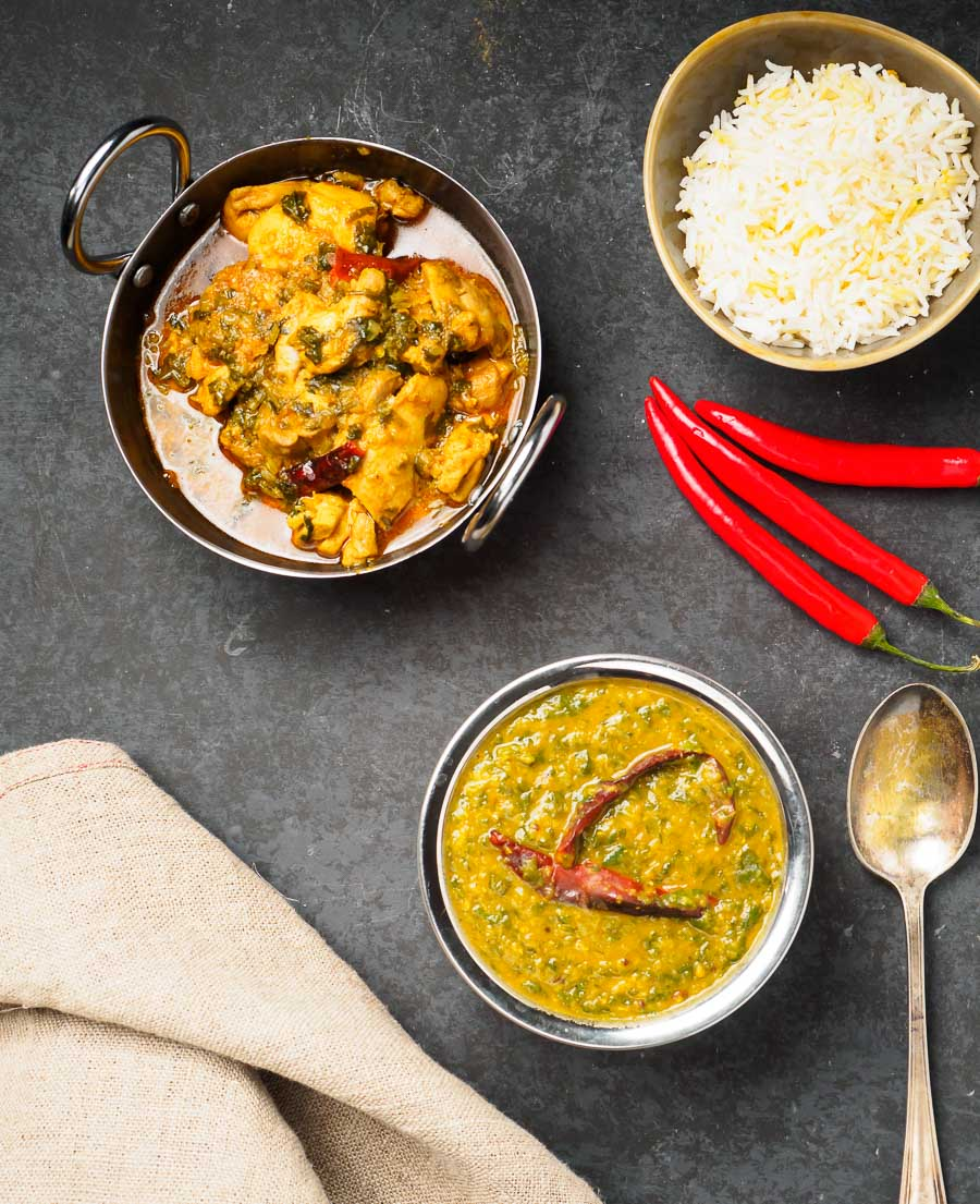 Dal palak, lemon chicken with coriander and rice in bowls from above.