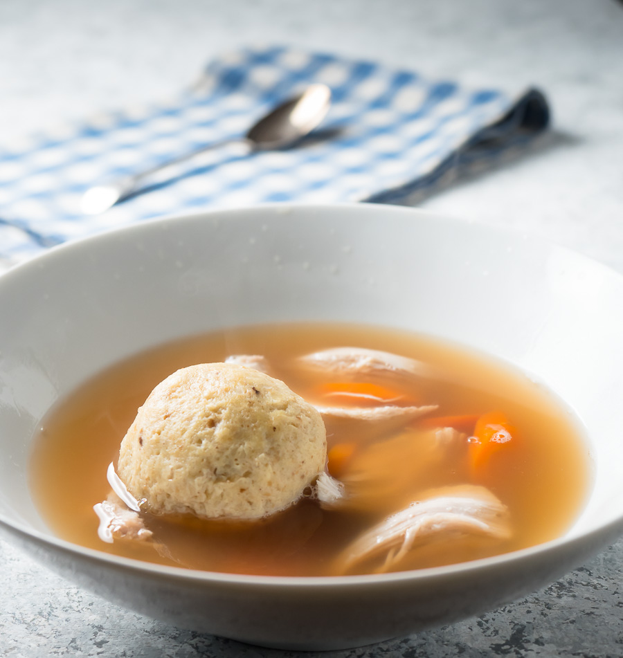 Matzo ball soup in a white bowl from the front.