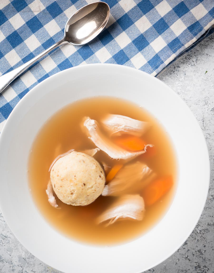 Matzo ball soup in a bowl from above.
