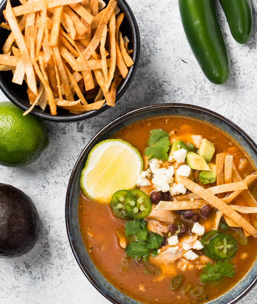 Chicken tortilla soup in a blue bowl from above.