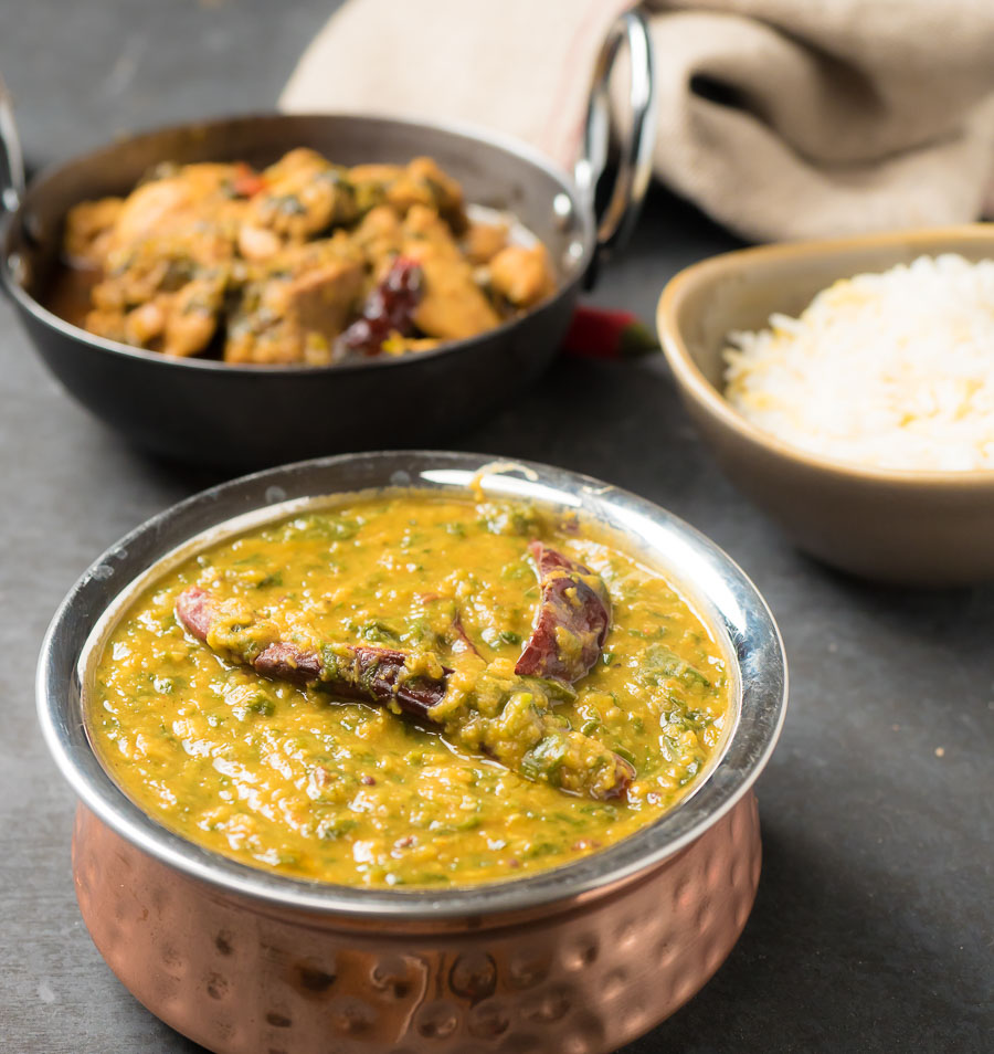 Dal palak in a copper bowl with curries and rice.