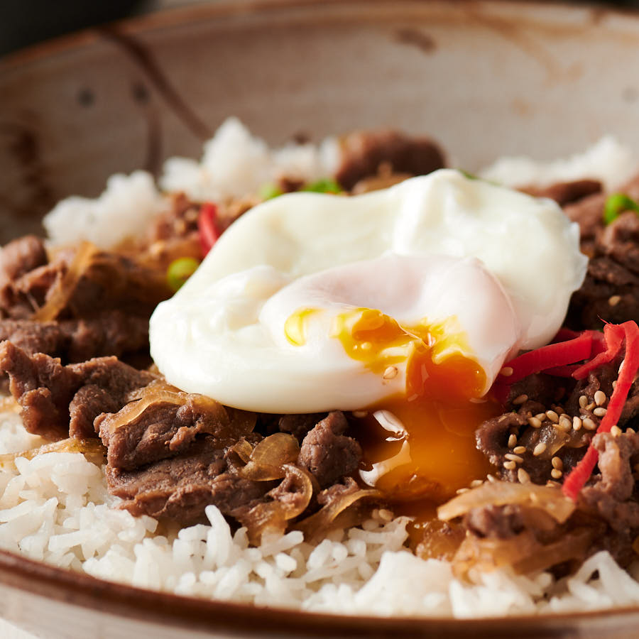 Poached egg on gyudon with yolk dripping into the beef.