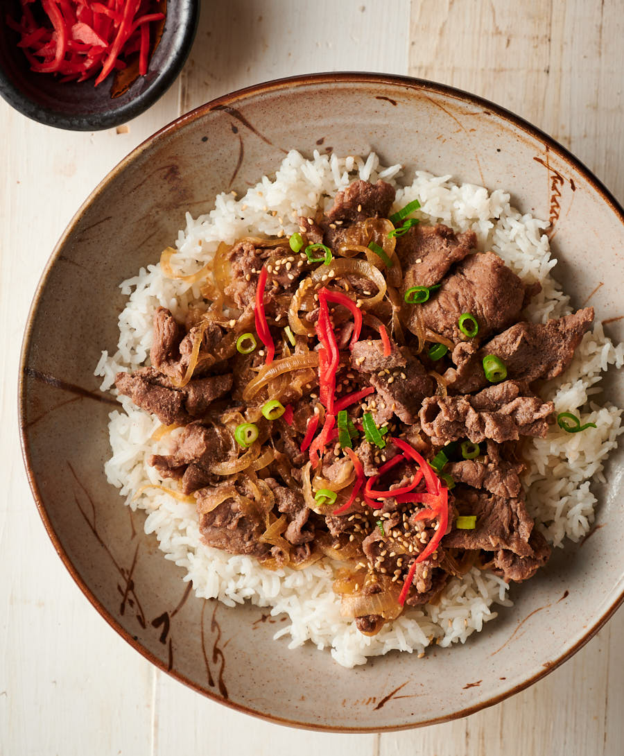 Overhead view of gyudon on rice in a bowl.