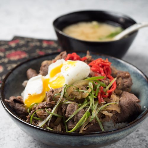 Broken poached egg with runny yolk on beef gyudon bowl.