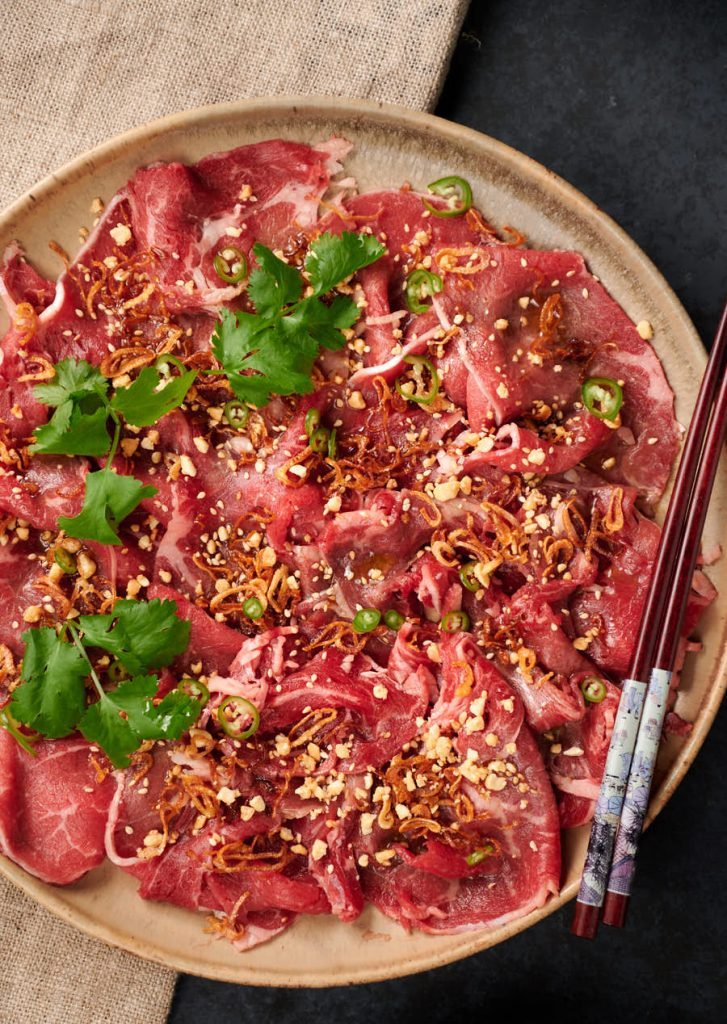 Platter of Asian style carpaccio garnished with sesame, peanuts, cilantro and green chili slices.