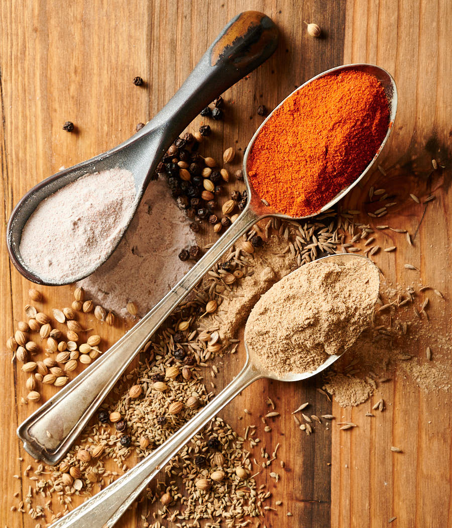 Chaat masala spices in spoons and on wood board.