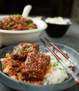Korean beef stew with rice on a dark plate with chopsticks.
