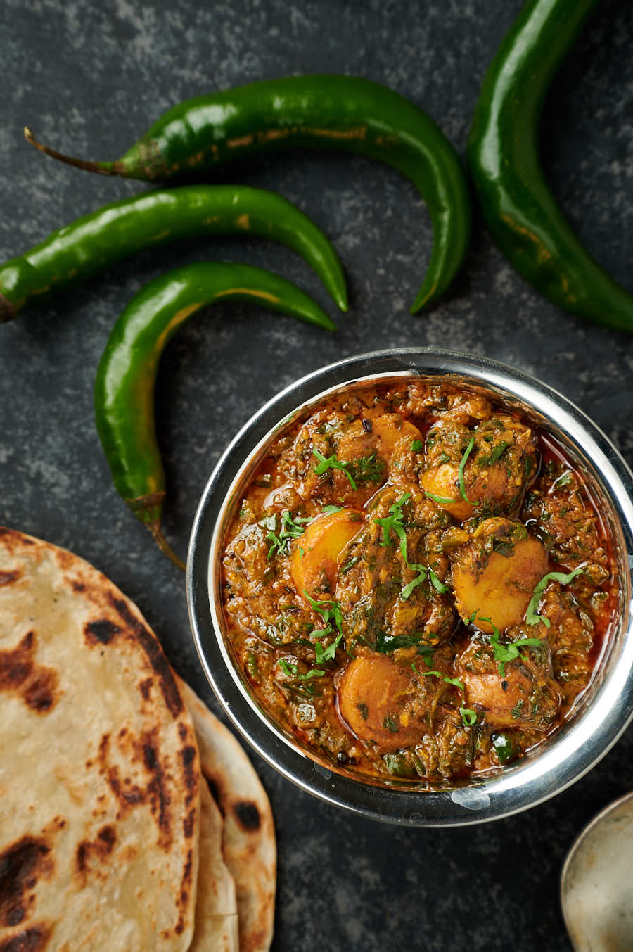 Saag aloo in a bowl surrounded by green chilies and parathas.