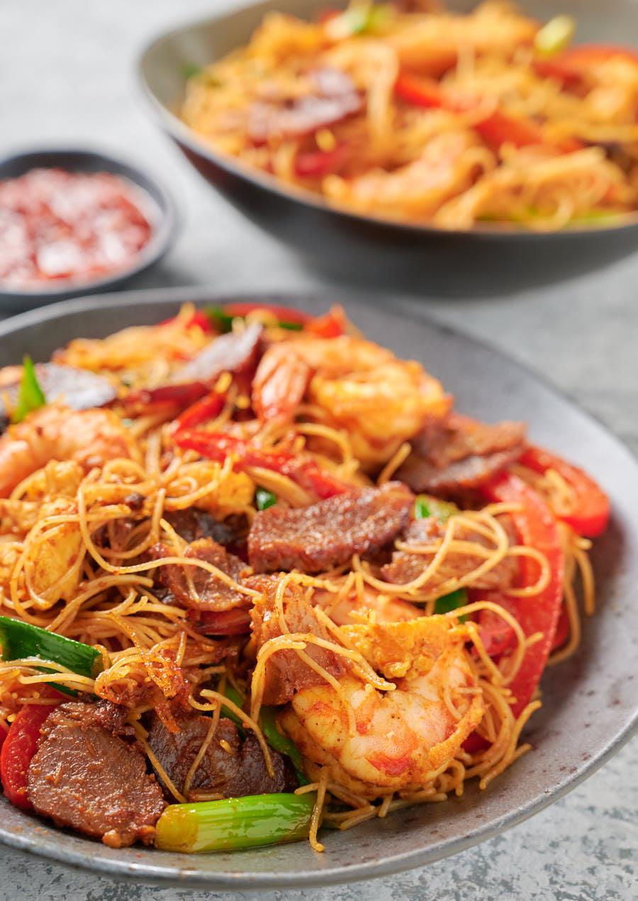 Singapore noodles with lots of pork, shrimp and egg on a plate