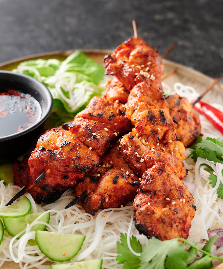 Spicy chicken skewers on a platter.