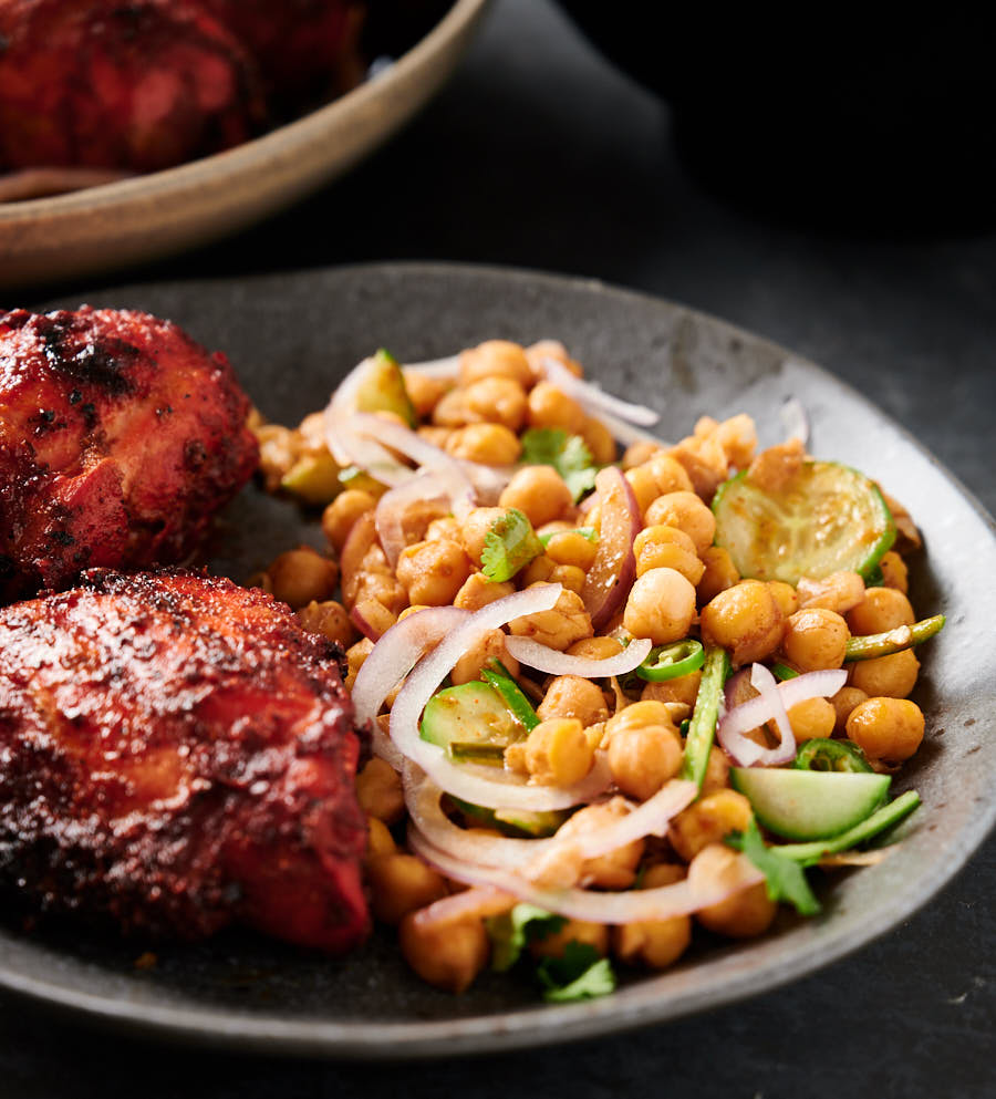 Plate of chana chaat with tandoori chicken from the front (close up).