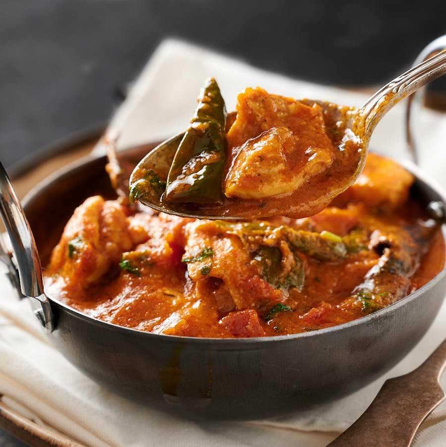 Spoonful of chicken masala over bowl of curry.
