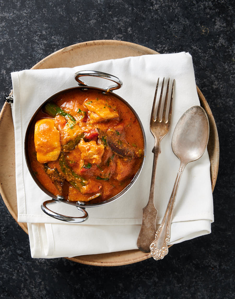 Bowl of chicken masala on a white napkin on a plate from above.