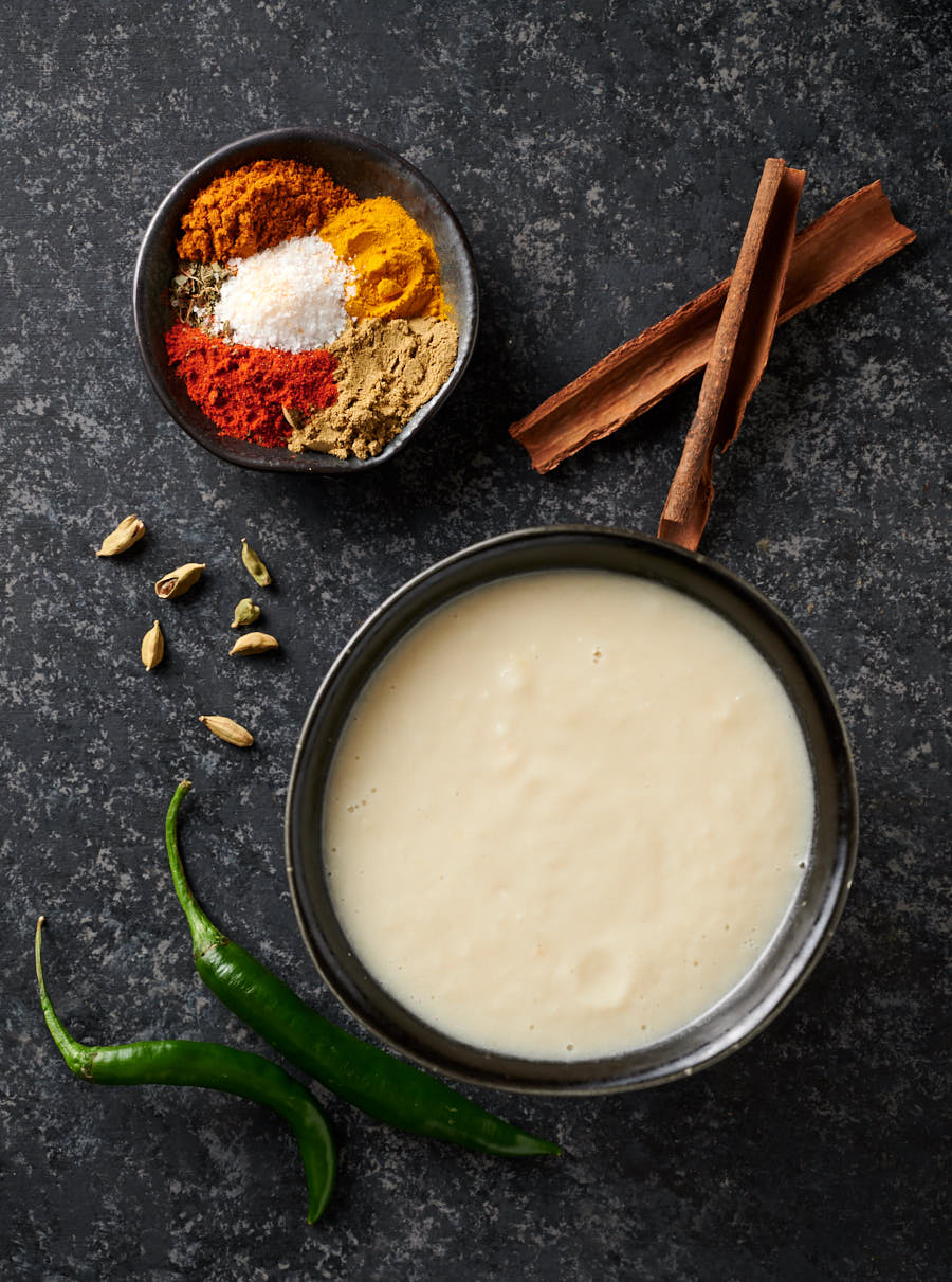 Moody overhead shot of onion paste and chicken masala spices.