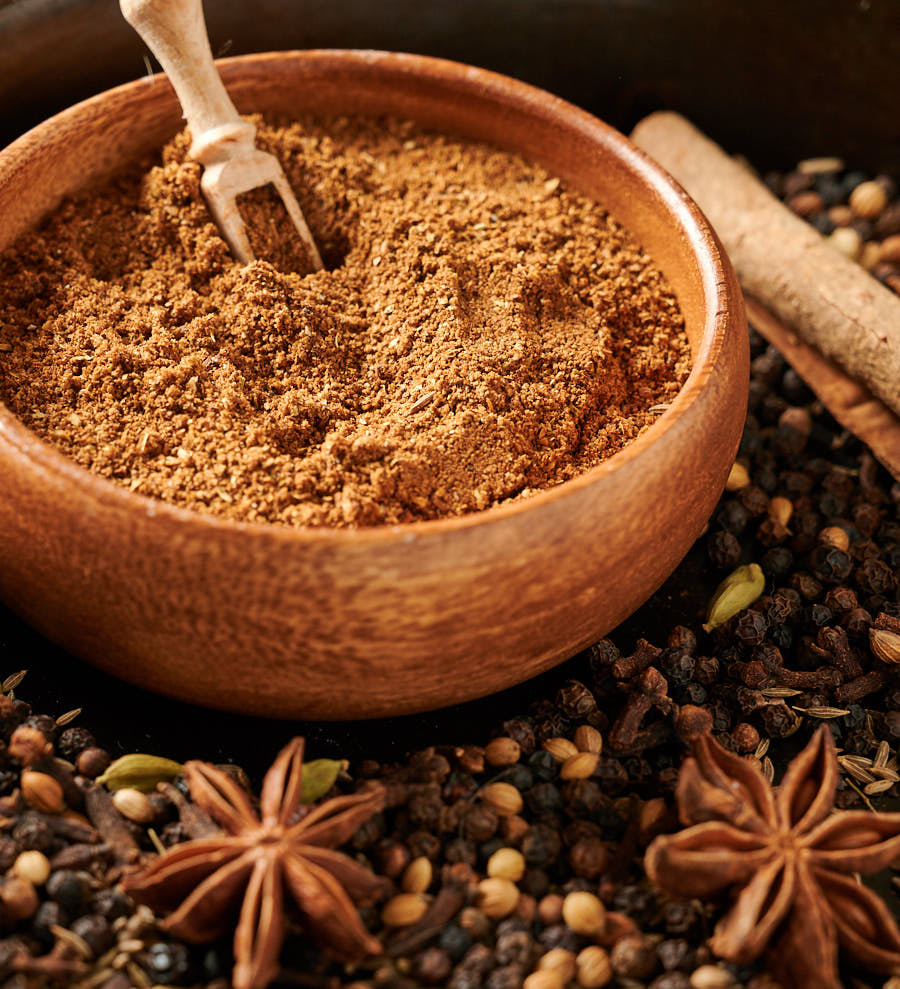 Bowl of garam masala surrounded by whole spices.