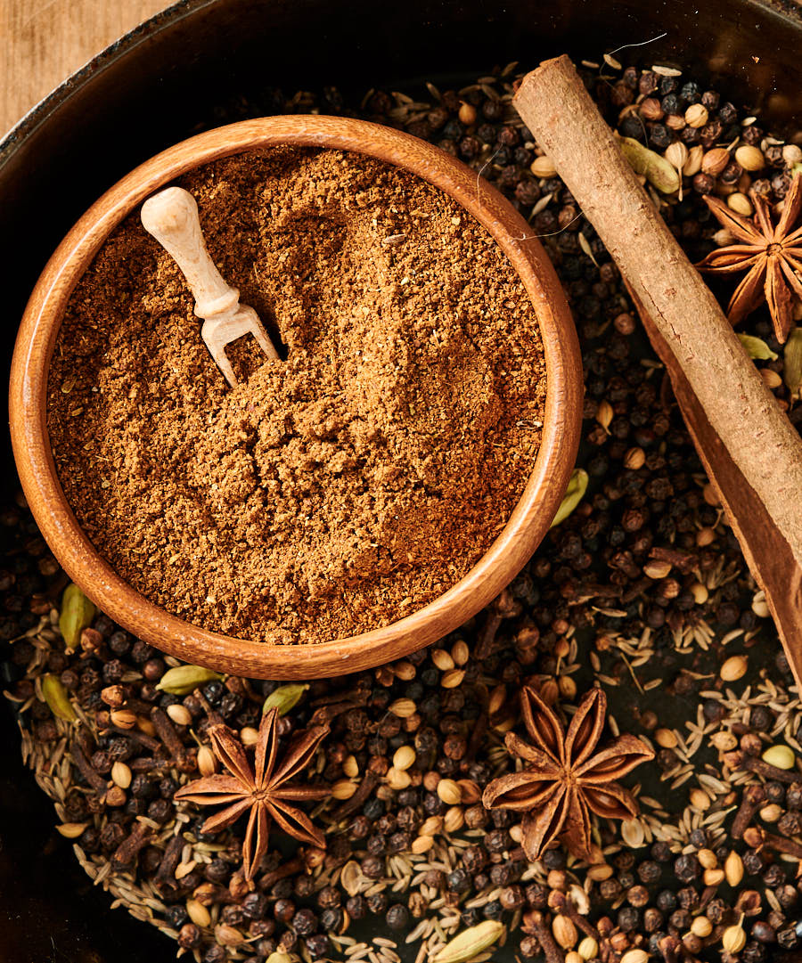 Bowl of garam masala surrounded by peppercorns, cumin seed, cinnamon and star anise from above.