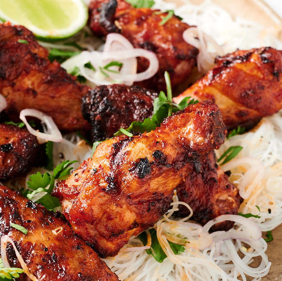 Close up of Korean chicken wings on rice noodles from the front.