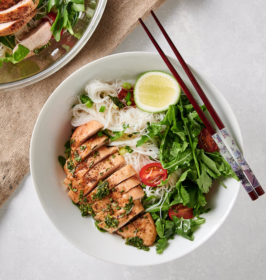 Thai chicken salad with rice noodles in a white bowl with chopsticks.