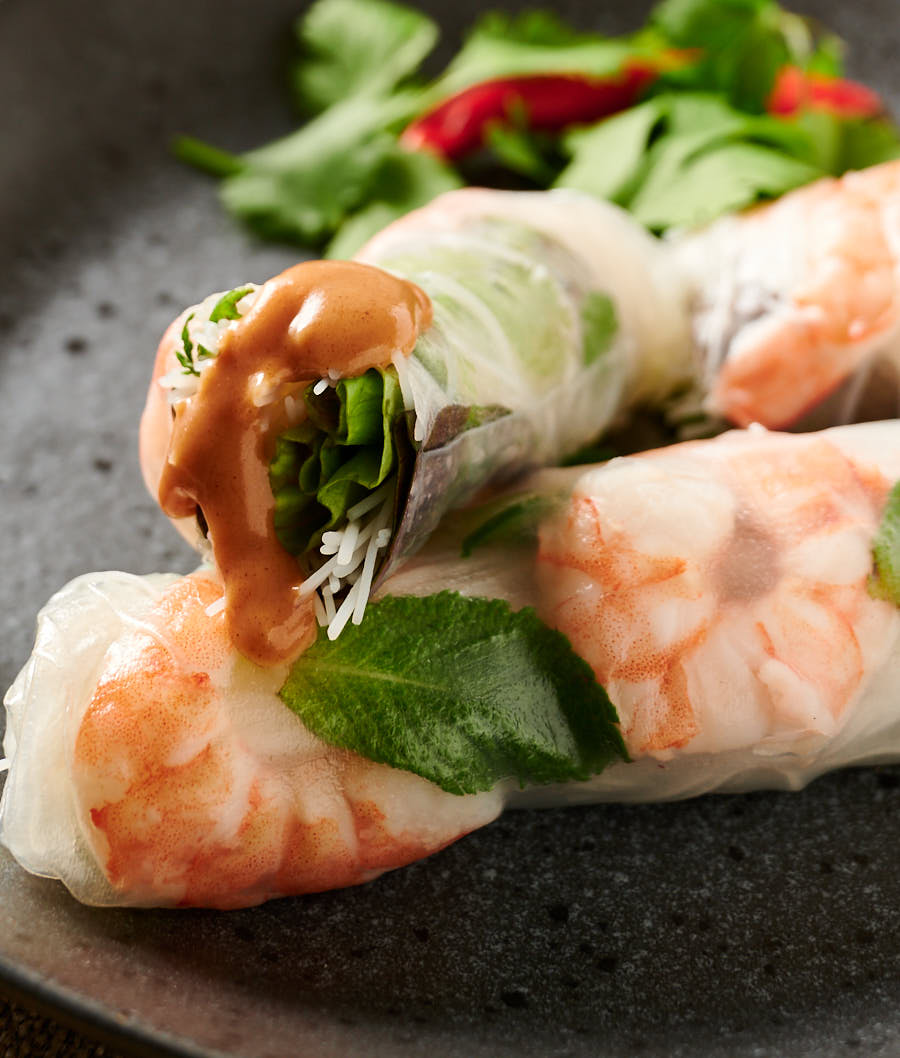 Cut Vietnamese spring roll with a drizzle of peanut sauce.