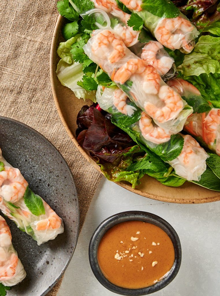 Overhead view of Vietnamese spring rolls on a platter and plate.