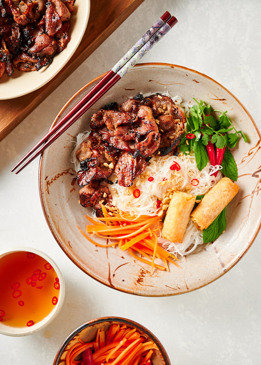 Table scene with grilled pork, pickled carrots, and nuoc cham.