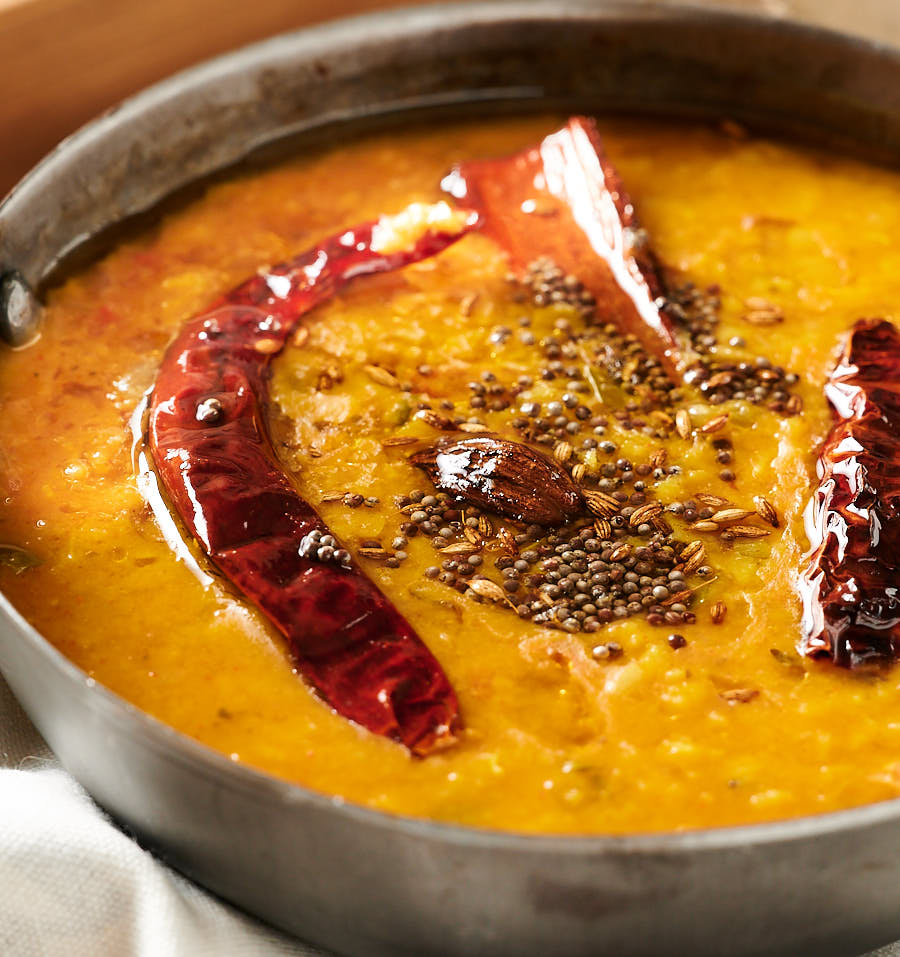 Close up of dal tadka with whole spices tempering.