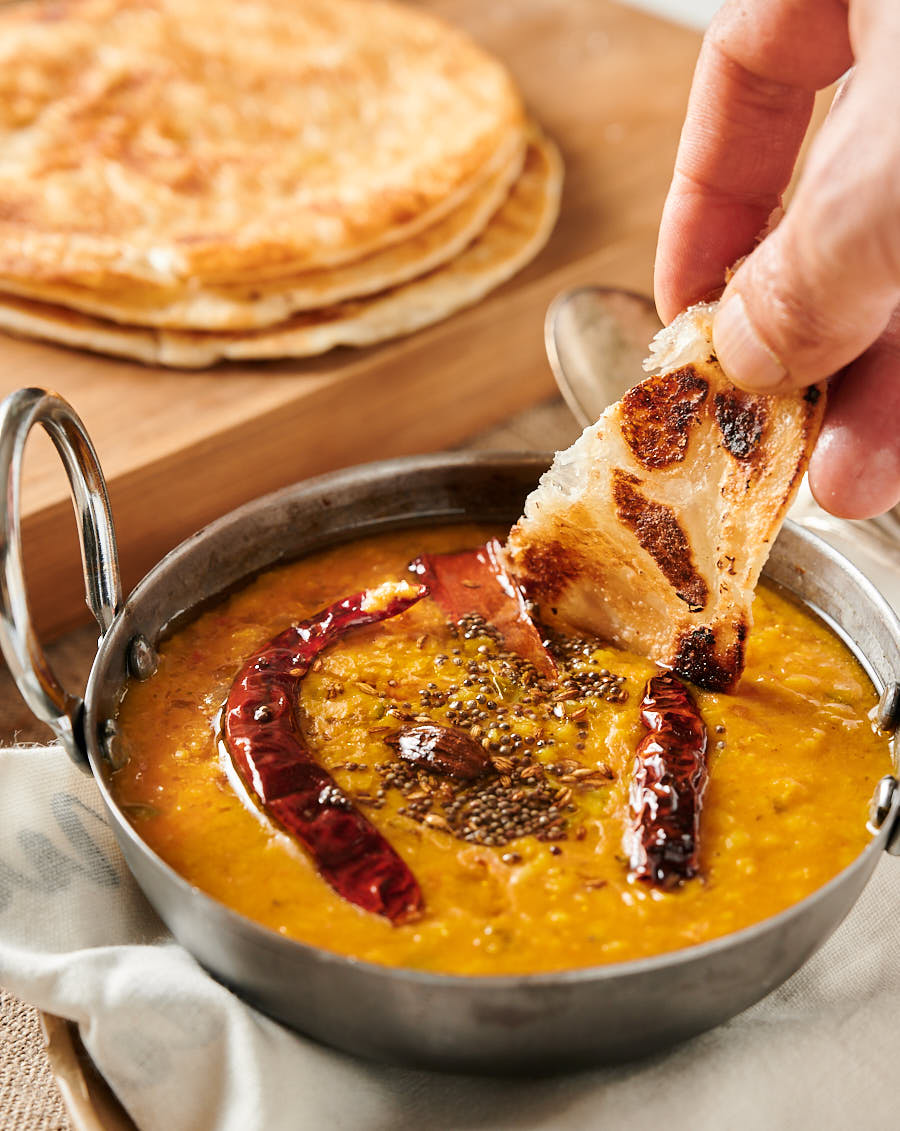 Dipping paratha into dal tadka.