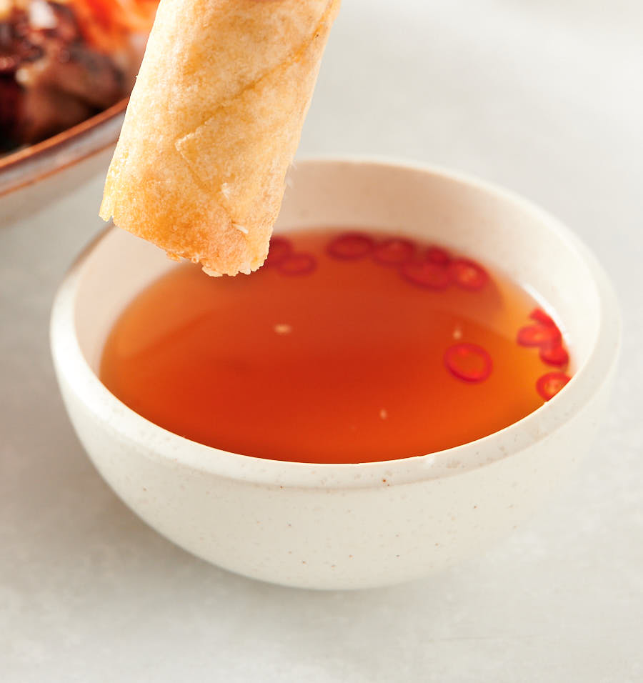 Spring roll held above bowl of nuoc cham.