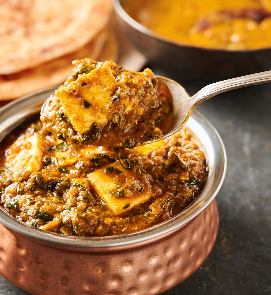Close-up of a spoonful of palak paneer.