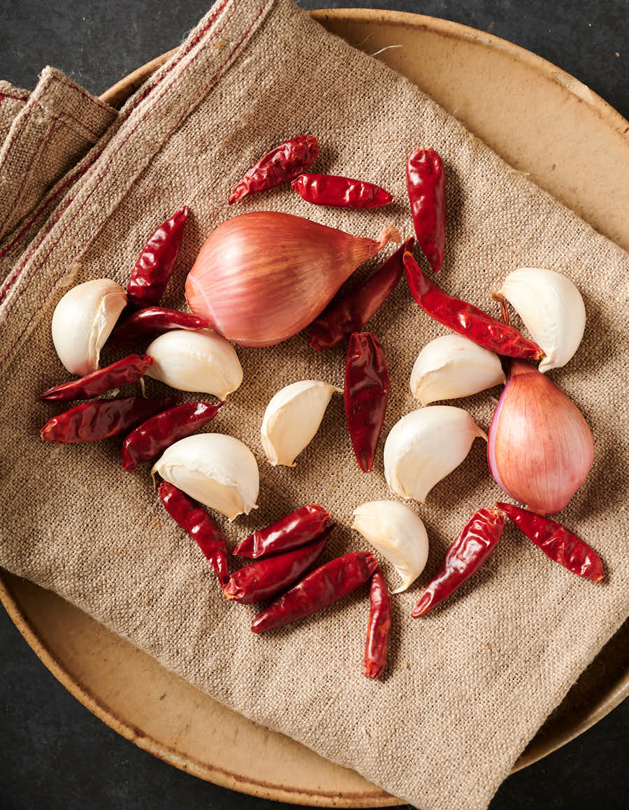 Garlic, chilies and shallots on a tan dishtowel from above.