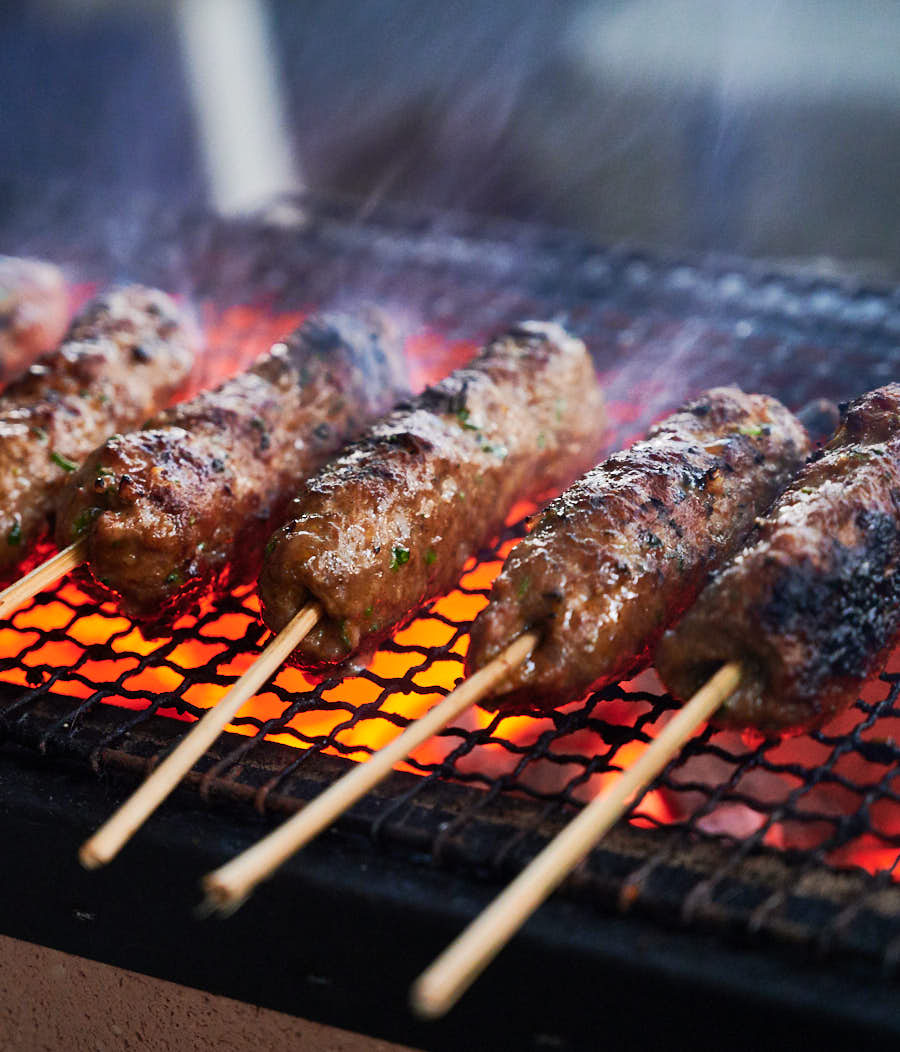 Indian seekh kebab cooking on a grill.