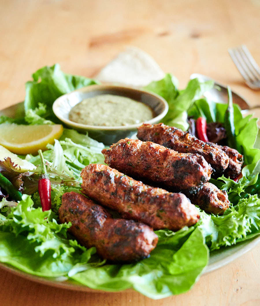 Indian seekh kebab on a plate with garnishes and dip from above.