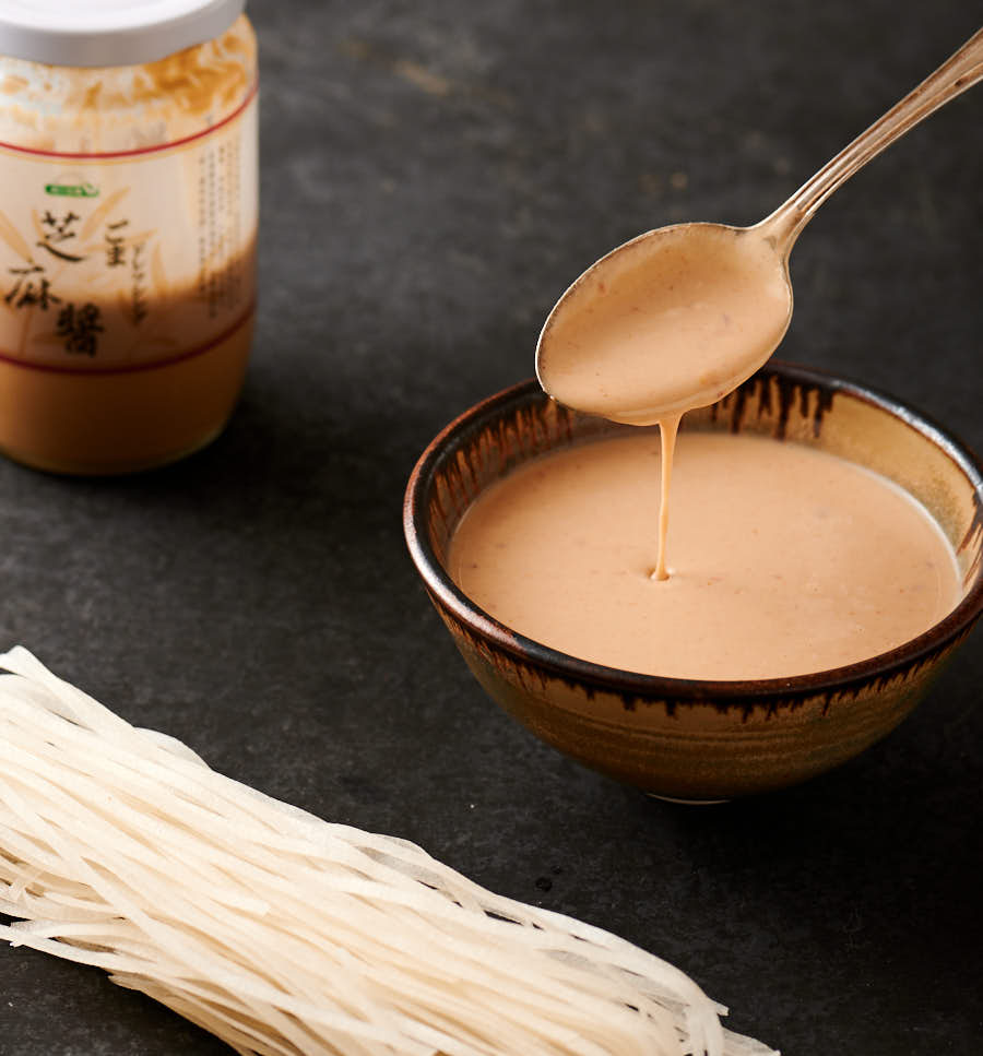 Sesame noodle sauce drizzled from a spoon