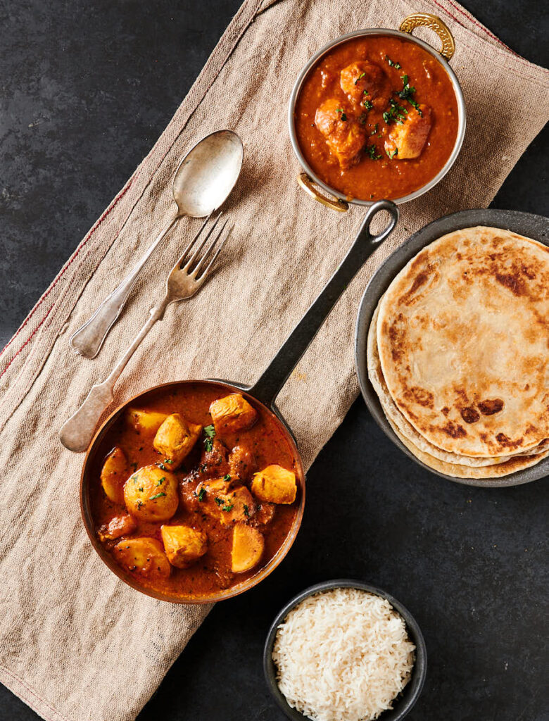 Bengali chicken curry with parathas and dhansak table scene from above.