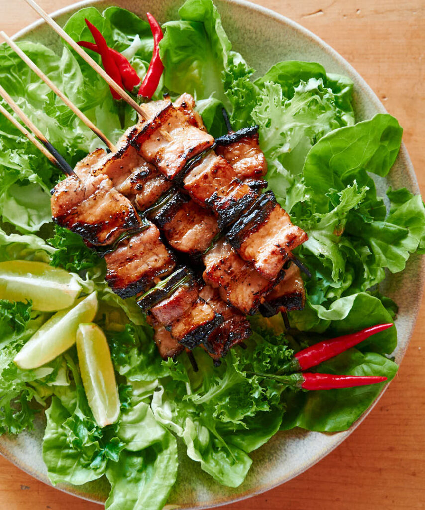 Grilled pork belly on a bed of lettuce with red chilies and lime wedges