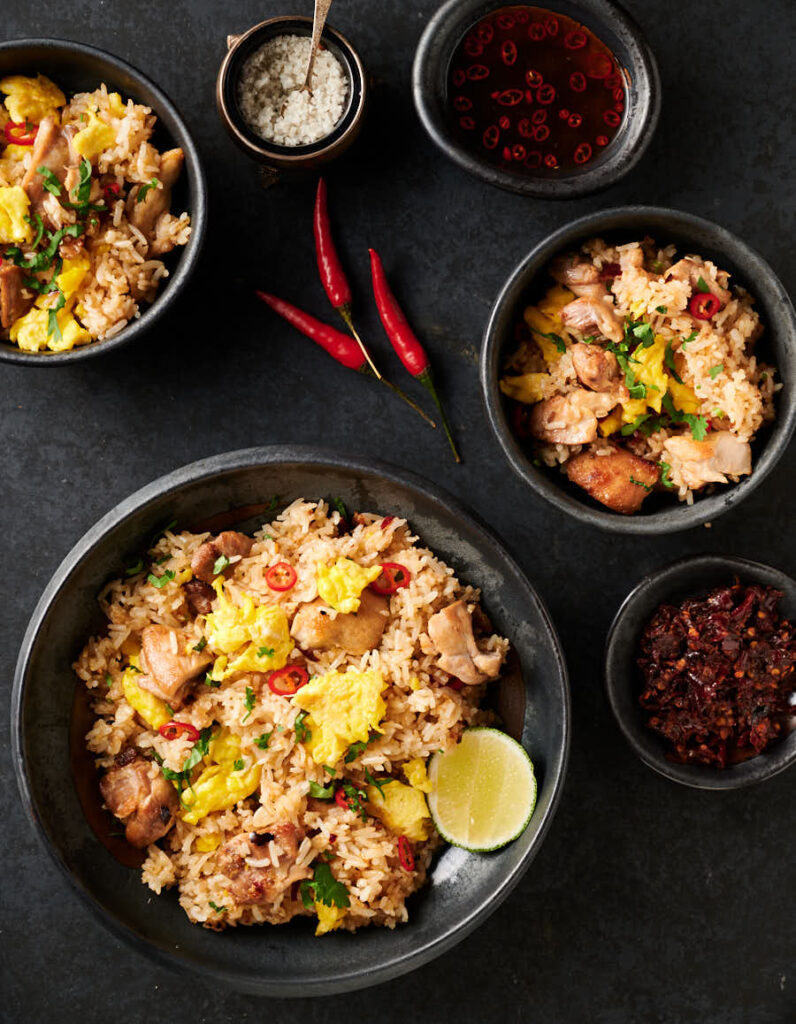 Thai fried rice bowl with garnishes surrounding it - from above.
