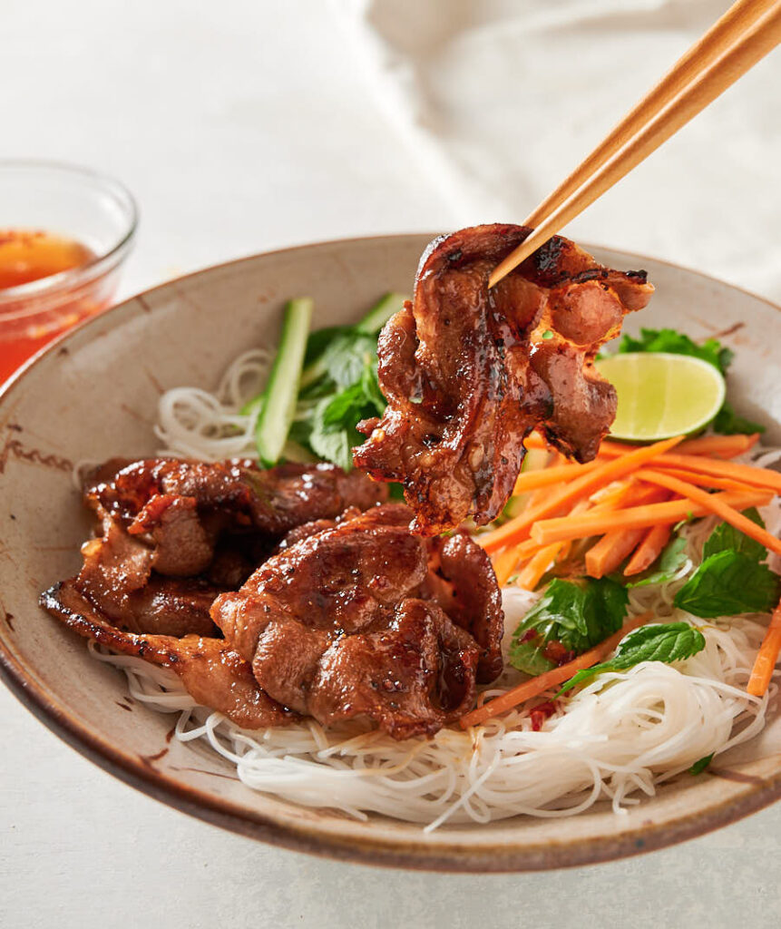 Chopsticks holding a piece of pork over a Vietnamese noodle salad bowl from the front.