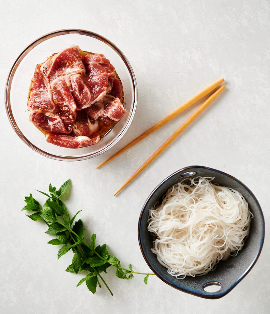 pork in marinade and bowl of cooked rice noodles