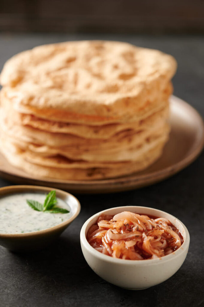 Red onion chutney in front of stack of papadum