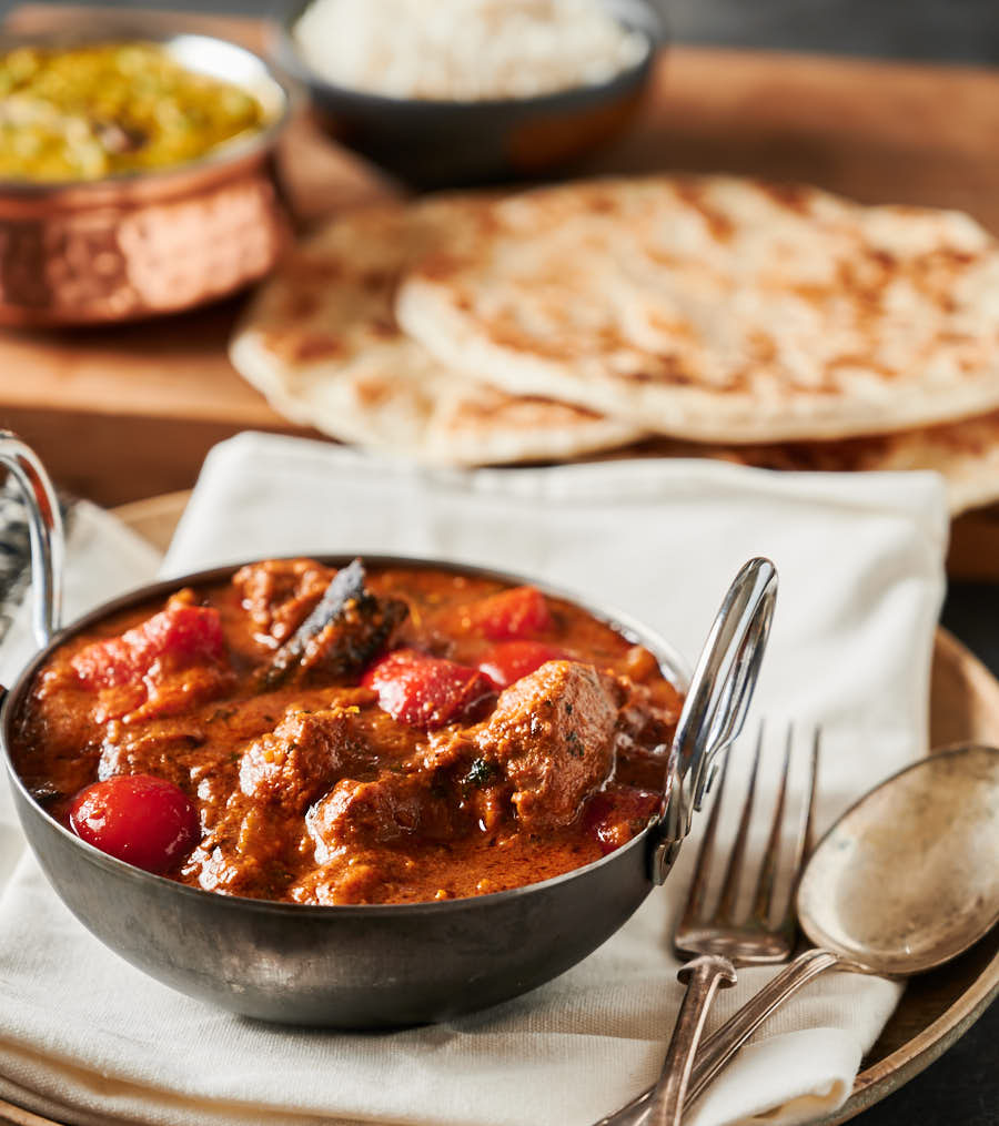 Lamb rogan josh in a black bowl with parathas from the front.
