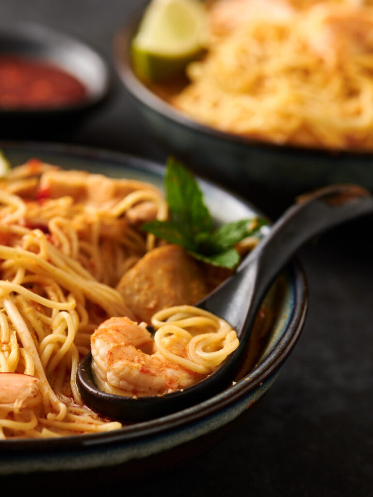 Spoon with shrimp and noodles from the front.