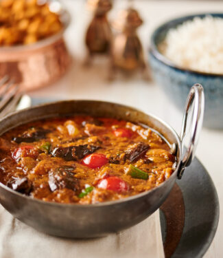 Eggplant curry in an iron bowl with rice and chana masala from the front.
