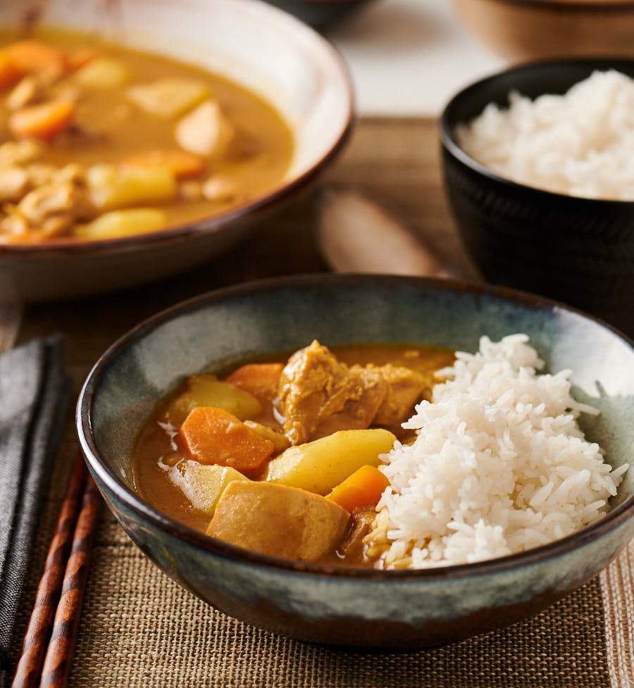 Bowl of Japanese chicken curry with rice with big bowl of curry in the background.