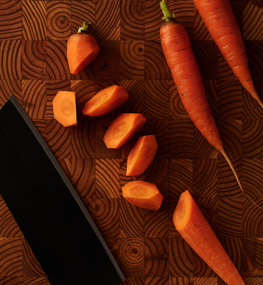 Rangari cut carrots and Japanese knife on a wood board from above.