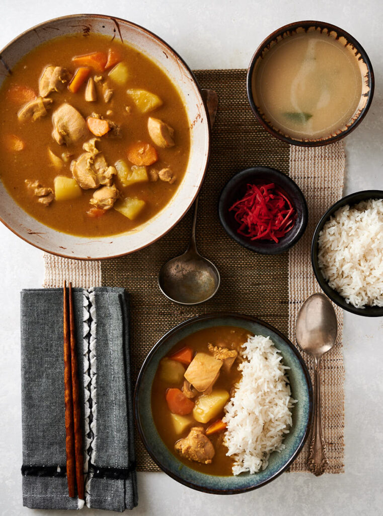 Table scene of Japanese chicken curry. Rice. Bowl of curry. Pickles. And plate with rice and curry.