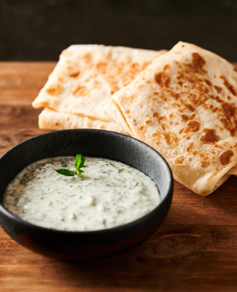 Bowl of mint raita in front of a couple mutton roti from the front.